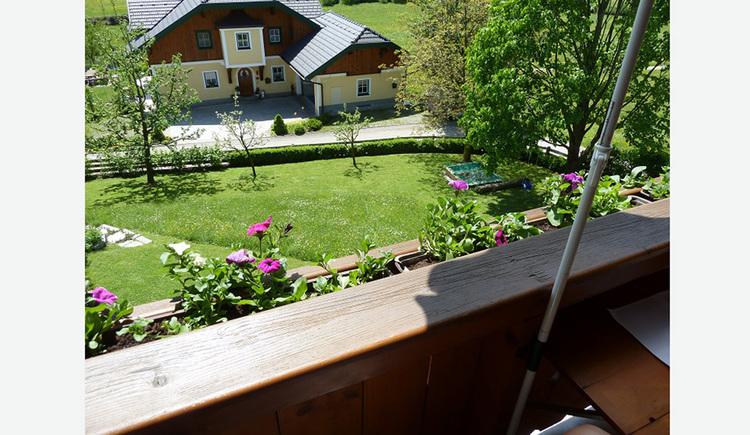 Blick vom Balkon auf den Garten, Wiese, Bäume, dahinter ein Haus