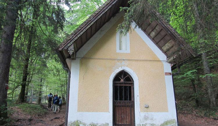 Blick auf eine kleine Kapelle mitten im Wald