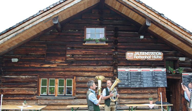 Rottenhofhütte mit zwei Musikanten im Vordergrund