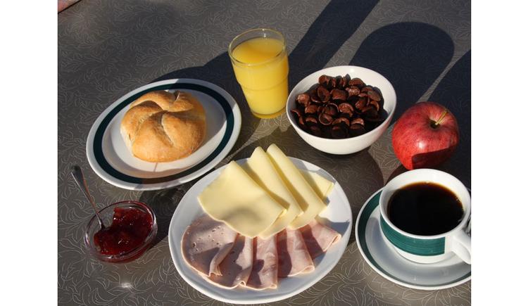 Frühstück: Wurst, Käse, Marmelade, Semmel, Orangensaft, Cornflakes, Apfel, Kaffee