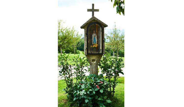 Blick auf den Bildstock, Heiligenfigur, Kreuz, im Vordergrund Pflanzen