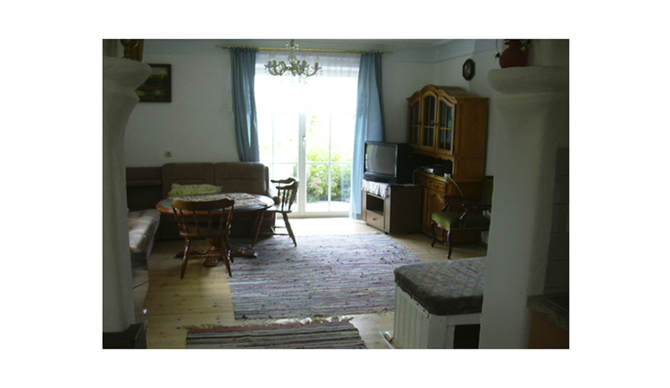 Wohnbereich mit Eckbank, Tisch und Stühle, im Hintergrund Balkontür, Fernseher, Kommode