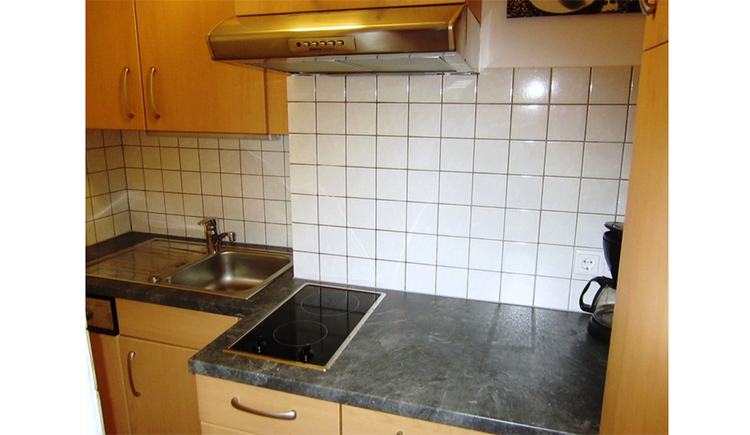Kitchen with coffee machine, stove, sink