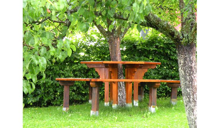 Garten mit Tisch und Bank rund um einen Baum. (© Winter)