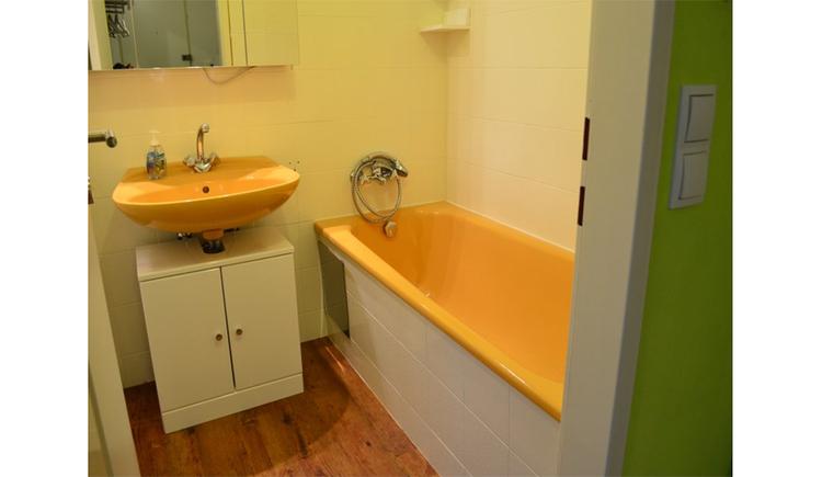 Badezimmer mit Waschbecken, Unterschrank, Spiegelschrank, seitlich eine Badewanne