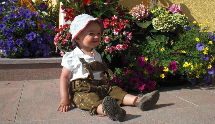 """Toddler sitting in \""""Lederhosen\"""" in front of flowers"""