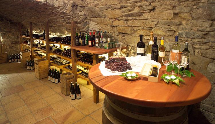 Weinkeller mit Weinregalen und Tisch mit Weinflaschen und Weingläsern