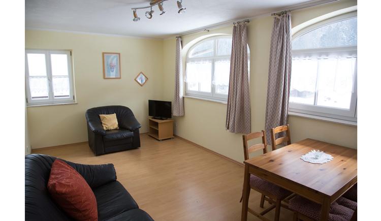 Wohnbereich mit Tisch und Stühle, seitlich Fenster, im Hintergrund ein Sessel, Couch