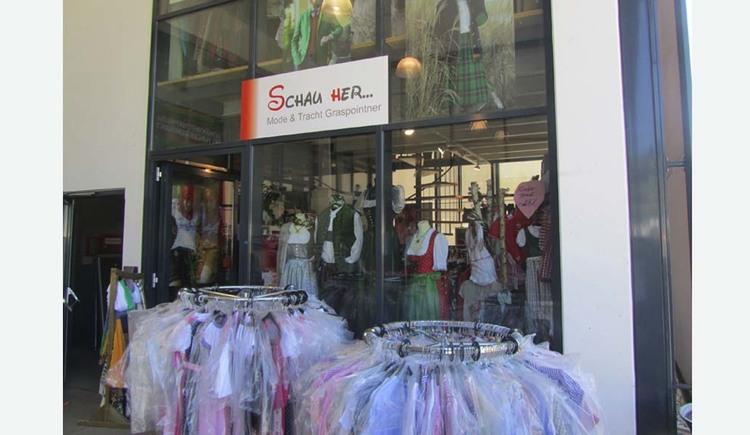 Blick auf den Geschäftseingang mit Glasfronten, davor Ständer mit Kleidung in Plastikhülle