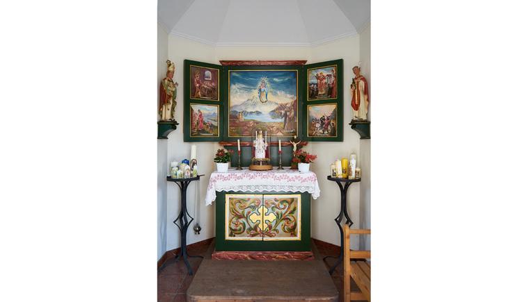 Blick auf den Altar, geschmückt mit Kerzen, Marienbilder