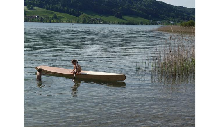 SUP-Board im See, Personen, im Hintergrund die Landschaft
