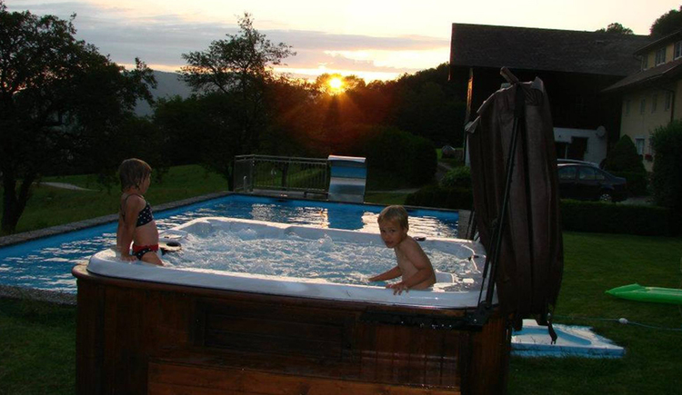 Kinder sitzen bei Sonnenuntergang im Whirlpool, dahinter das Schwimmbad
