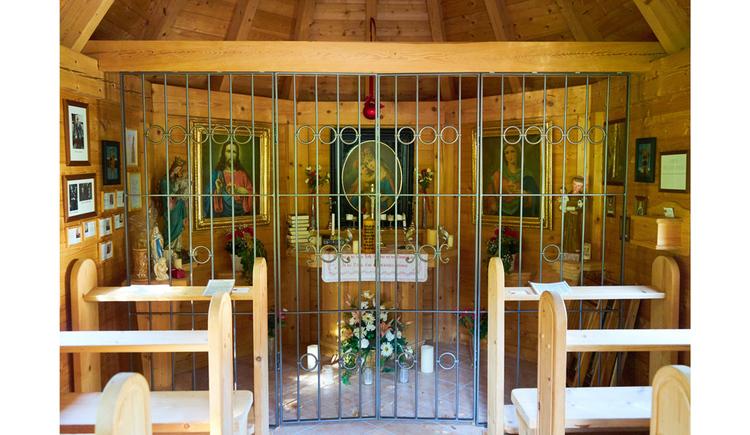 Blick in die Kapelle, mit Holzbänken, dahinter ein Gitter vor dem Altar