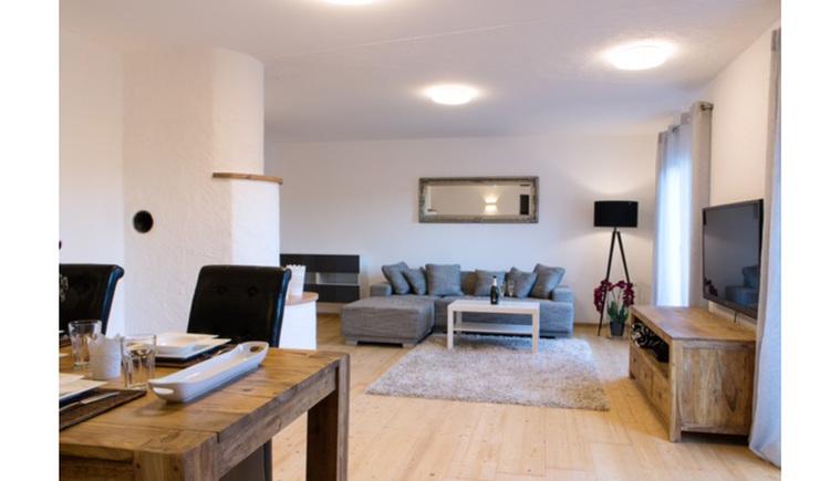 Wohnbereich mit Tisch und Stühle, im Hintergrund Couch und kleiner Tisch, Lampe, seitlich eine Kommode mit Fernseher