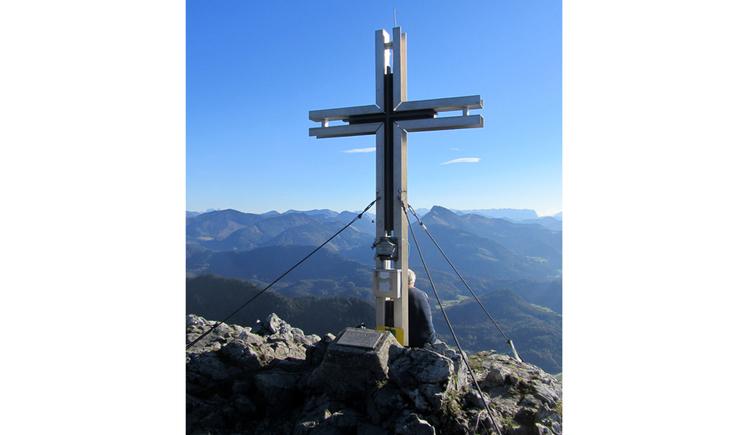 Blick auf ein Kreuz, im Hintergrund Berge