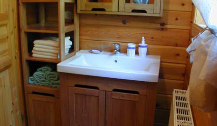 Das Badezimmer mit viel Holz ausgestattet, bietet eine Dusche und Waschtisch. (© Rehn)