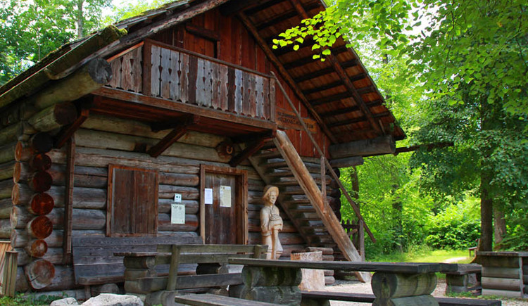 Here you can see the Museum of Wood cutters in the so called Müllnerwald. Next to the door you can see a wooden wood cutter. In front view wooden seats.