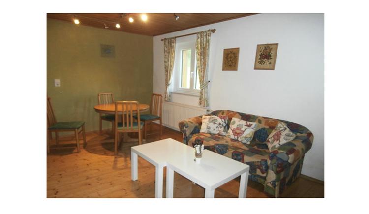 kleine Couch mit Tischen, im Hintergrund ein Esstisch und Stühle, Fenster, Bilder an der Wand