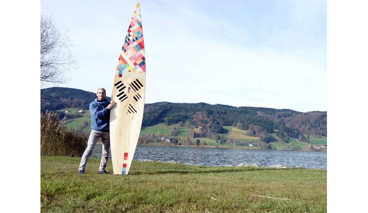 Person steht mit einem SUP-Borad in der Wiese, im Hintergrund der See und die Landschaft
