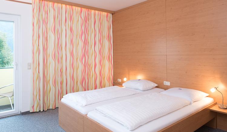 Zimmer mit Doppelbett, Nachttisch mit Lampe, Balkontür mit Zugang zum Balkon und Vorhang