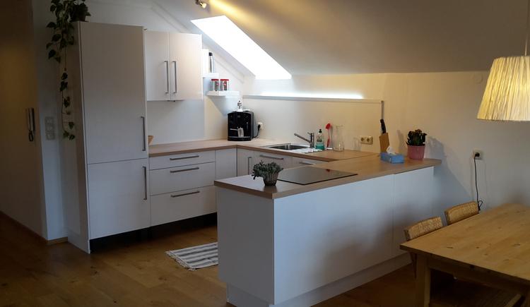 Blick in die Küche mit Kaffeemaschine, Spüle, Herd, seitlich im Vordergrund Tisch mit Stühlen