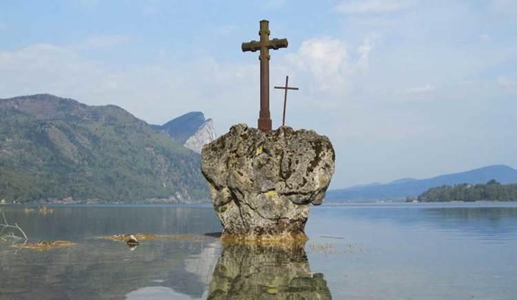 Blick auf den Stein mit dem Kreuz darauf (Kreuzstein), rundherum der See, im Hintergrund die Berge. (© www.mondsee.at)