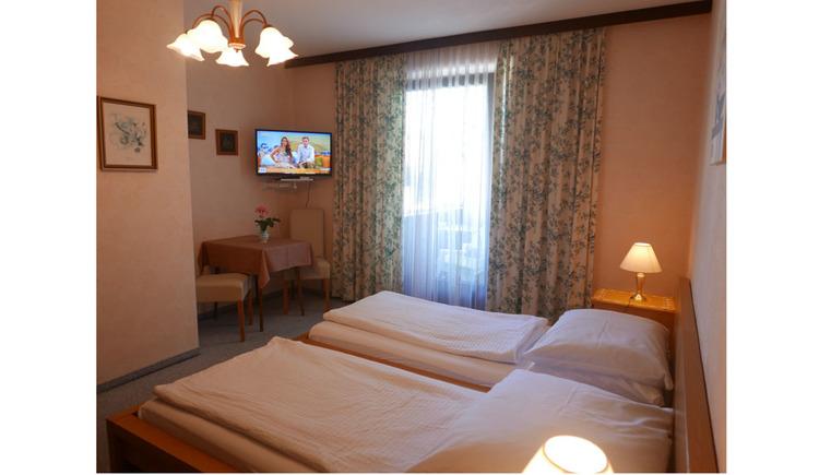 Schlafzimmer mit Doppelbett, Nachtkästchen mit Tischlampe, im Hintergrund Tisch mit Stühlen, im Eck ein Fernseher an der Wand, Balkontür