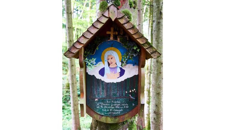 Blick auf das Holzmarterl mit einem Marienbild an einem Baum. (© Matthias Winkler)