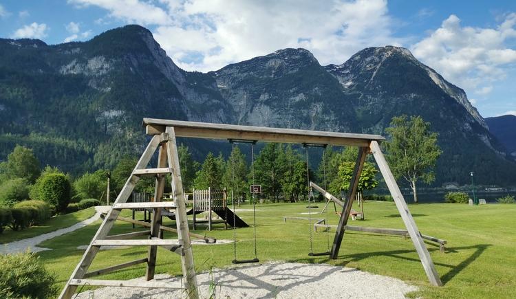 Das Foto zeigt die beiden Schaukeln vom Spielplatz und die wunderschöne Bergkulisse im Hintergrund. (© Ferienregion Dachstein Salzkammergut)