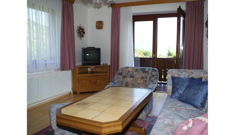 Wohnbereich: seitlich Couch mit Polster, Tisch, Sessel, im Hintergrund Kommode mit Fernseher, Fenster und Balkontür