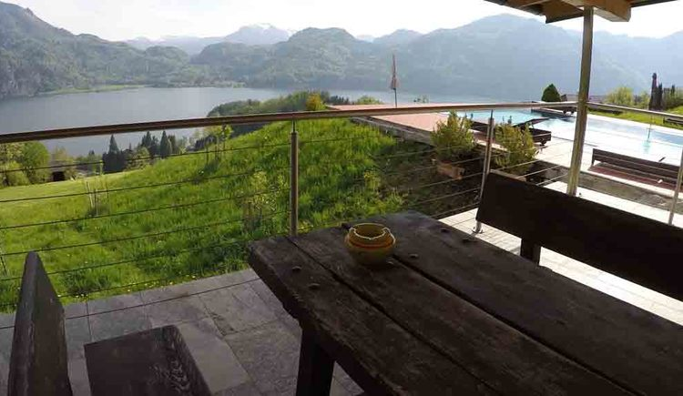 terrace with table and benches, on the side the pool, in the background the lake and the mountains\n