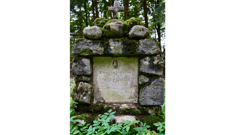 Blick auf das Marterl umgeben von Steinen mitten in einem Wald
