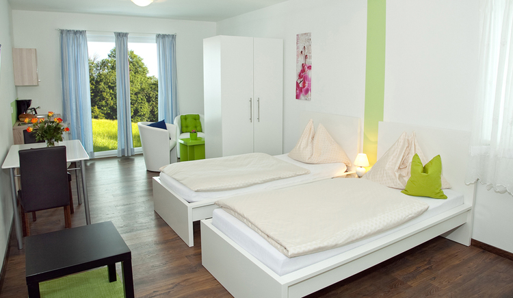 Schlafzimmer mit zwei Einzelbetten, Nachtkästchen mit Lampe, Kleiderschrank, dahinter Sitzgelegenheit mit Tisch, seitlich eine kleine Kochgelegenheit, im Hintergrund Balkontüre