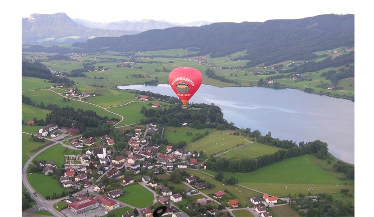Luftaufnahme auf den Ort, umgeben von Landschaft, seitlich der See und die Berge. (© Tourismusverband MondSeeLand)