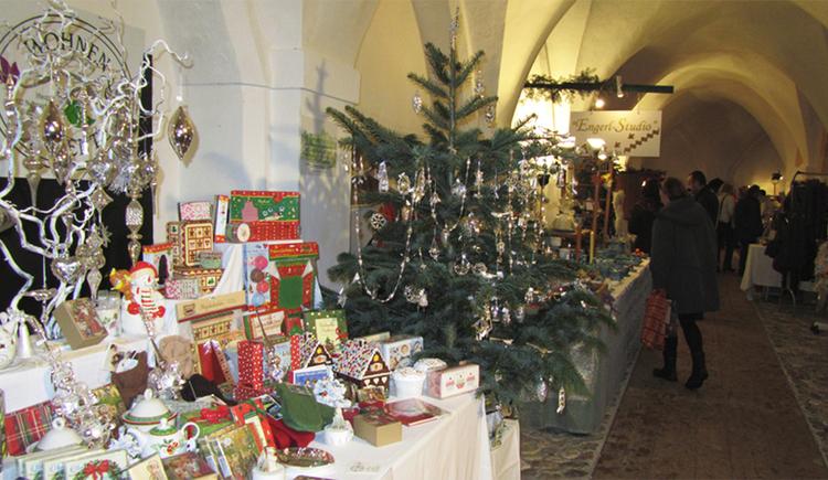 Stand mit kleinen Geschenken, Christbaum mit Schmuck im Hintergrund