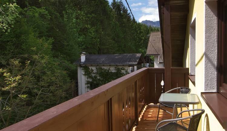 Vom Balkon blicken sie auf den Wald und die umliegende Bergwelt