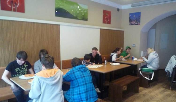 Innenbereich mit Tischen und Stühlen, gemütliches Beisammensitzen bei einer Pizza