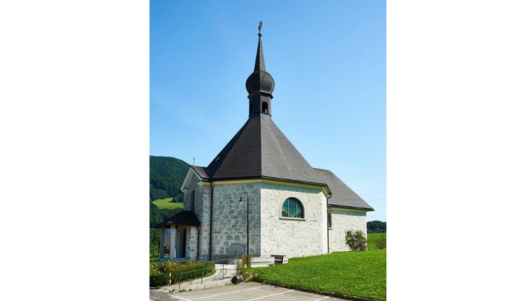Blick auf die Kirche, im Vordergrund eine Wiese