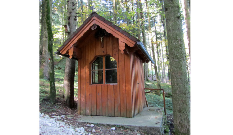 Blick auf die Holzkapelle mitten im Wald