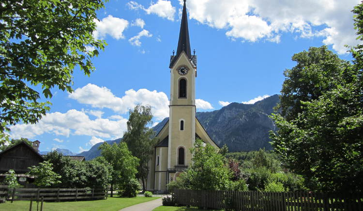 Here you will see the front view of the yellow church with the main door and the tower of the church surrounded by trees and bushes. In the Background the mountains as well as a blue sky with some clouds.
