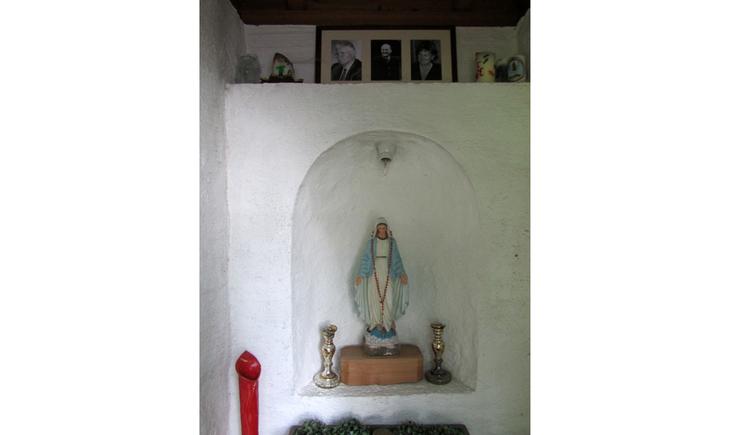 Blick auf eine Heiligenfigur, darüber Fotos