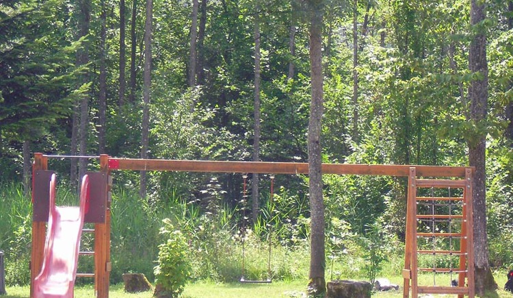 Schaukel mit Rutsche am Kinderspielplatz in Untersee - im Hintergrund Wald