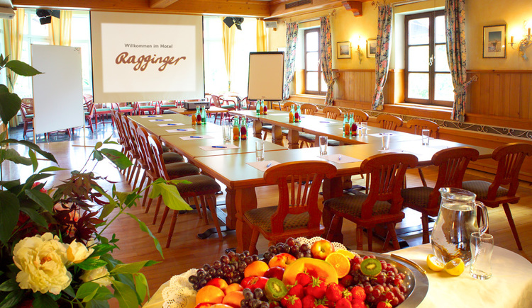 Seminarraum mit Leinwand und großem Tisch. (© Familie Ragginger/Klaus Costadedoi)