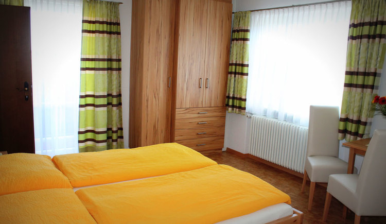 Double bed, wardrobe, balcony door, in the background a window, table with chairs