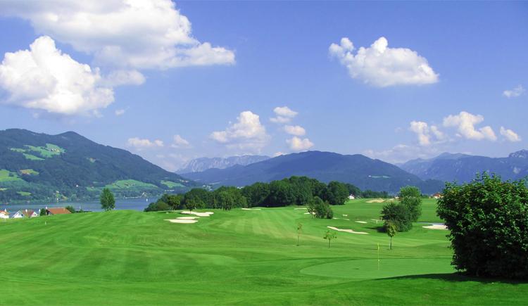 Blick auf den Golfplatz, im Hintergrund Bäume, der See und die Berge