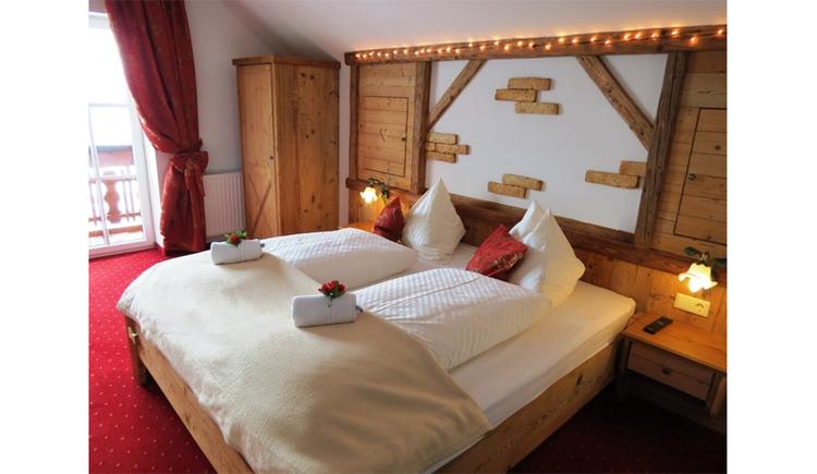 Schlafzimmer mit Doppelbett, Rosen auf dem Bett, Nachtkästchen, Lampen, seitlich eine Balkontür und Kleiderschrank