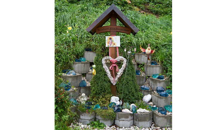 Holzkreuz, im Hintergrund eine Wiese, bepflanzte Steine