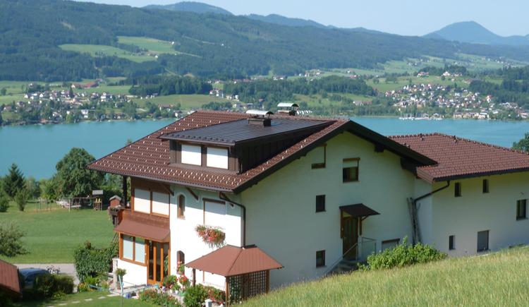 Ausblick auf das Haus von Hinten, im Hintergrund der See und die Berge