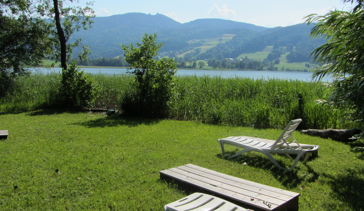 Garden with sunbeds in front of the lake Irrsee and mountains.