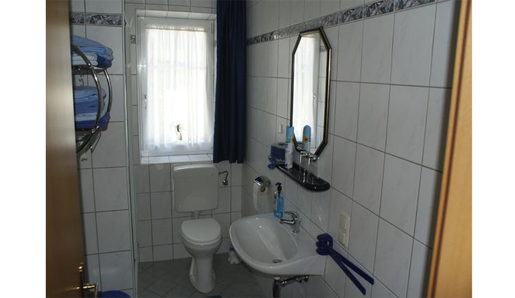 seitlich ein Waschbecken mit Spiegel, im Hintergrund Toilette und ein Fenster